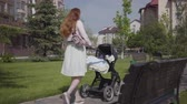 decree : Beautiful red-haired woman walking on the walking along a stone walkway with a pram in the park. The lady enjoying the sunny day with her baby outdoors. Young mother walking with a child