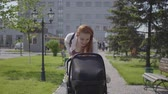 decree : Young happy redhead mother walking with baby carriage and smiling along the street on a nice spring day