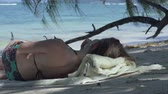 resort : Seychelles. Praslin Island. Young girl lying in the shade of palm trees listens to music on the shores of an exotic island located in the Indian Ocean. Tropical island luxury vacation. Stock Footage