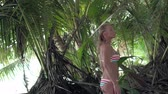 bronzeada : Seychelles. Praslin Island. Beautiful woman in a swimsuit looks around standing among palm trees on an exotic island in the Indian Ocean. Stock Footage