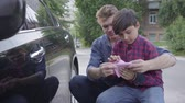 hombres : Young father teaching his son to care about the car. The man and a boy wiping the machine with a rag close-up. A man passes on knowledge to a son, teaching him to be careful with auto
