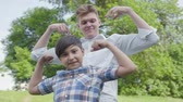 бицепс : Young father and the boy showing muscles looking into the camera outdoors close-up. Father and a kid having fun in the park. Friendly family spends time together. Bottom view