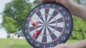 ダーツ : The father hands holding darts while his son throwing darts and ball on a magnet in the circles close-up. Family leisure outdoors. Father and a kid spend time together