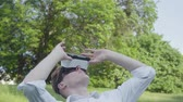 hombres : Young man wearing virtual reality headset walking in the park, looking at sides and up, enjoying the realistic image. Modern technologies. The guy playing video game