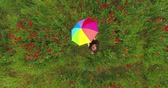 girlish : View from above of cute young girl under colorful umbrella dancing in a poppy field smiling happily looking in the camera. Connection with nature. Leisure outdoors, summertime fun