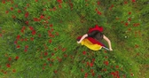 mák : View from above of young girl dancing in a poppy field holding flag of Germany in hands outdoors. Connection with nature, patriotism. Leisure in nature. Blossoming poppies. Freedom.