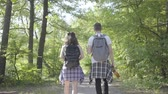 mundo : Portrait man and young cute girl walking in the forest. Pair of travelers with backpacks outdoors. Leisure couples. Journey to nature. Stock Footage