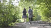 mundo : Portrait of guy and young cute girl walking in the forest. Pair of travelers with backpacks outdoors. Leisure couples. Journey to nature.
