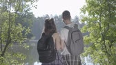 mundo : Portrait couple standing on the riverbank in the forest with backpacks pointing away. The young man and woman hiking. Concept of camping. Leisure couples. Journey to nature. Stock Footage