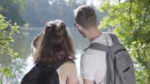 mundo : Portrait of guy and young cute girl standing on the riverbank in the forest with backpacks pointing away. The young man and woman hiking. Concept of camping. Leisure couples. Journey to nature. Stock Footage