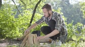 mundo : Portrait confident traveler puts firewood for the fire. Handsome man in a plaid shirt prepares to make a fire outdoors. Concept of camping. Leisure and journey to nature. Stock Footage