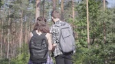 mundo : Portrait of guy and young girlfriend walking in the forest. Pair of travelers with backpacks outdoors. Leisure couples. Journey to nature.