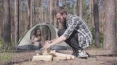 mundo : Handsome man in a plaid shirt prepares firewood to make a fire outdoors. The girl sits in a tent and plays the ukulele or guitar. Concept of camping. Leisure and journey to nature.