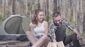 kindle : The young man kindling a fire in the forest while pretty young woman sitting near. Loving couple resting outdoors. Concept of camping. Leisure and journey to nature.