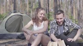 kindle : Portrait young man kindling a fire in the forest while adorable young woman sitting near. Loving couple resting outdoors. Concept of camping. Leisure and journey to nature. Stock Footage