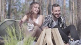 tenda : Portrait handsome young man kindling a fire in the forest while beautiful young woman sitting near. Loving couple resting outdoors. Concept of camping. Leisure and journey to nature. Stock Footage