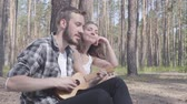 mundo : Portrait handsome bearded young man playing ukulele while pretty young happy woman sitting near. Loving couple having fun outdoors. Concept of camping. Leisure and journey to nature.
