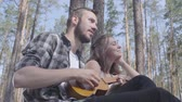 mundo : Portrait attractive bearded young man playing ukulele while pretty young happy woman sitting near. Loving couple having fun outdoors. Concept of camping. Leisure and journey to nature. Stock Footage