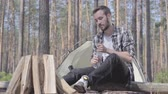 mundo : Young handsome man sitting in front of pieces of wood for the fire, drinking water from the plastic bottle. The tent on the background. Unity with wild nature. The guy is camping Stock Footage