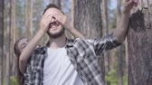 mundo : Portrait of handsome young man in the pine forest, the girl covering his eyes with hands from behind close-up. Unity with wild nature. The couple resting outdoors Stock Footage