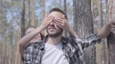 mundo : Portrait handsome bearded young man in the pine forest, the girl covering his eyes with hands from behind close-up. Unity with wild nature. The couple resting outdoors Stock Footage