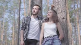 mundo : Portrait of handsome young man and pretty woman looking away standing in the pine forest. Concept of camping. Leisure and journey to nature. Cute couple outdoors. Stock Footage