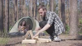 mundo : Portrait of bearded handsome man in a plaid shirt prepares firewood to make a fire outdoors. The girl sits in a tent and plays the ukulele or guitar. Concept of camping. Leisure and journey to nature.