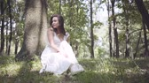 Portrait cute young girl with long brunette hair wearing a long white summer fashion dress sitting under a tree in the park. Leisure of a pretty woman outdoors with soft sunset natural light. Vidéos Libres De Droits