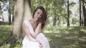 Portrait of cute young girl with long brunette hair wearing a long white summer fashion dress sitting under a tree in the park. Leisure of a pretty woman looking at the camera outdoors.