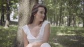 Portrait glamorous young girl with long brunette hair wearing a long white summer fashion dress sitting under a tree in the park. Leisure of a pretty woman looking at the camera outdoors. Stock Footage