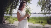 ромашка : Portrait of cute young girl with long brunette hair wearing a long white summer fashion dress standing in the park. Leisure pretty woman holding a bouquet of chamomile looking at the camera outdoors. Стоковые видеозаписи