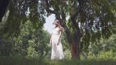 Portrait adorable young girl with long brunette hair wearing sunglasses and a long white summer fashion dress standing under the branches of a tree in the park. Leisure a pretty woman outdoors. Filmati Stock