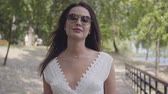 Portrait adorable young girl with brunette hair wearing sunglasses and long white summer fashion dress walking along a wooden bridge in the park. Leisure a pretty woman looking at the camera outdoors.