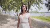 Portrait glamorous young girl with brunette hair wearing sunglasses and long white summer fashion dress walking along park. Leisure a pretty woman looking at the camera outdoors.