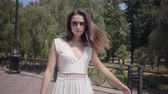 Beautiful young girl wearing sunglasses and a long white summer fashion dress walking outdoors. Leisure of a pretty woman turns around straightening hair and lookng into the camera. Slow motion.