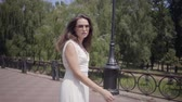 Cute young girl wearing sunglasses and a long white summer fashion dress walking outdoors. Leisure of a pretty woman turns around straightening hair and lookng into the camera. Slow motion.