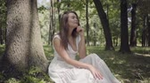 Portrait of glamorous young girl with long brunette hair wearing a long white summer fashion dress sitting under a tree in the park. Leisure of a pretty woman outdoors. Slow motion.