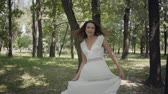 Charming young girl dressed in a white long summer dress spin in the park. Leisure of a pretty woman outdoors. Slow motion. Vidéos Libres De Droits