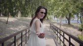 Portrait glamorous brunette young girl wearing sunglasses and long white summer fashion dress walking along wooden bridge. Pretty woman looking at the camera outdoors. Follow me. Gesture. Slow motion. Filmati Stock