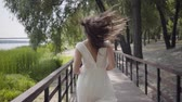 Lovely young girl with brunette hair wearing sunglasses and long white summer fashion dress running over a wooden bridge. Leisure a pretty woman outdoors. Slow motion.