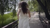 Portrait lovely young girl with brunette hair wearing sunglasses and long white summer fashion dress running over a wooden bridge. Leisure a pretty woman outdoor. Slow motion.