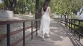 Portrait adorable young girl with brunette hair wearing sunglasses and long white summer fashion dress running over a wooden bridge. Leisure a pretty woman outdoors. Slow motion. Vidéos Libres De Droits