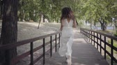 Portrait charming young girl with brunette hair wearing sunglasses and long white summer fashion dress running over a wooden bridge. Leisure a pretty woman outdoors. Slow motion.