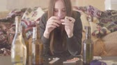 çatlak : The young unstable nervous addicted woman sitting on the sofa at home in front of the alcohol bottles and pills lying on the table. Unhealthy lifestyle. Troubled teens. Drug addiction