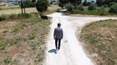 mírumilovný : Video from above of a man wearing jeans, a plaid shirt and sunglasses man walking along a country road. Dron pursues follow a man. Shooting from the drone.