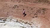 Man dressed in shorts, sneakers and a T-shirt walking along a cliff. Foamy waves hitting the rocky shore. Shooting from the drone. Cyprus. Vidéos Libres De Droits