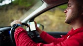 deneyimli : Portrait bearded young man driving a car holding a cell phone with a navigation map. Cyprus. Slow motion. Stok Video