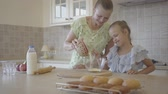 родитель : Pretty young mother and little cute daughter cook in the kitchen together. Happy family. Relationship mom and daughter. Стоковые видеозаписи