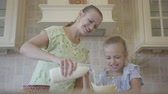biscoitos : Young smiling woman and her little daughter cooking cake at home in the kitchen. The girl mixing flour while mother pouring milk in the transparent bowl. Mom and child spending time together