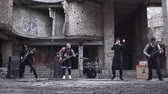 cantar : Rockers in gothic style and make-up playing metal rock with guitar and drum kit on the background of abandoned building